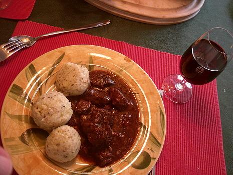 Gedeckter Tisch mit Kartoffelklößen, Gulasch, Rotwein