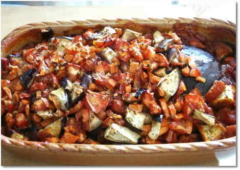 Aubergine, mit Knoblauch gespickt, mit Tomatensauce und Gemüse