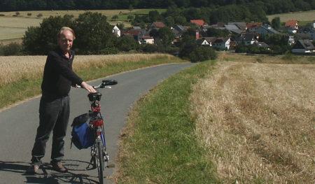 Webmaster samt Fahrrad, im Hintergrund Lenzhahn
